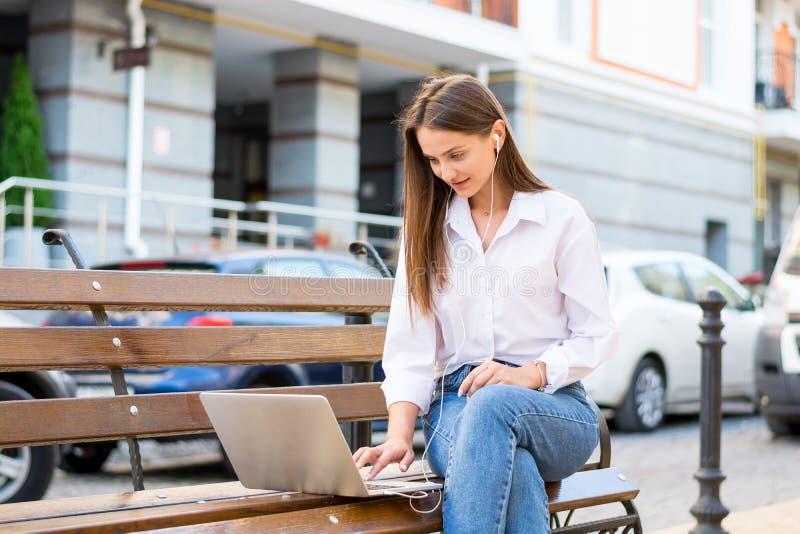 Het jonge mooie wijfje met laptop en in hoofdtelefoons zit op a stock afbeeldingen