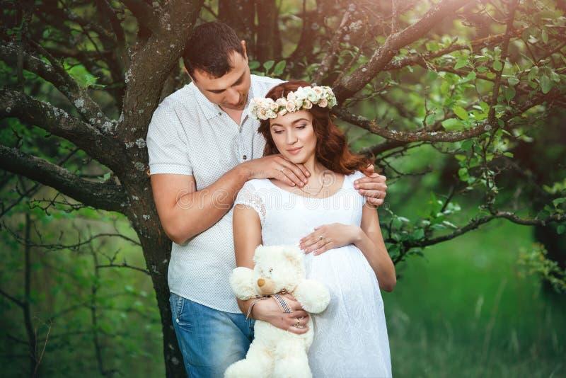 Het jonge mooie zwangere meisje met haar echtgenoot met stuk speelgoed draagt in groene tuin royalty-vrije stock foto