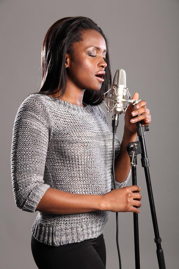 Het jonge mooie zwarte zingen in microfoon stock fotografie