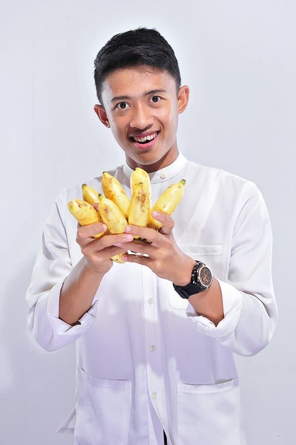 Het jonge moslimmens gelukkige vasten wanneer het breken van snelle Iftar en suhoor eten gele banaan stock fotografie