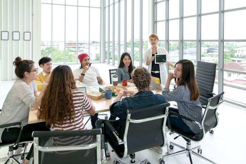 Het jonge multi-etnische diverse creatieve Aziatische groeps spreken of uitwisseling van ideeën in de workshop van de bureauverga stock foto's