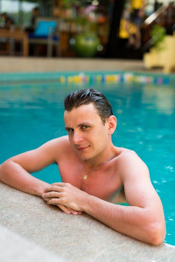 Het jonge natte mens stellen in het zwembad stock foto