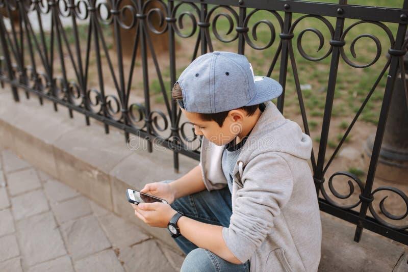 Het jonge online spel van het jongensspel bij smartphone buiten Jongenszitting in centrum van de stad De spelen van het jongenssp royalty-vrije stock afbeelding