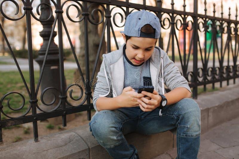 Het jonge online spel van het jongensspel bij smartphone buiten Jongenszitting in centrum van de stad De spelen van het jongenssp royalty-vrije stock foto's