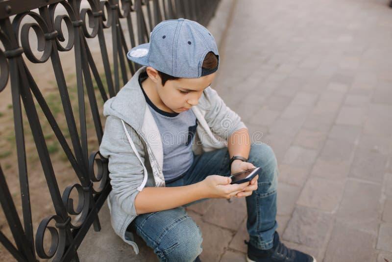Het jonge online spel van het jongensspel bij smartphone buiten Jongenszitting in centrum van de stad De spelen van het jongenssp royalty-vrije stock foto