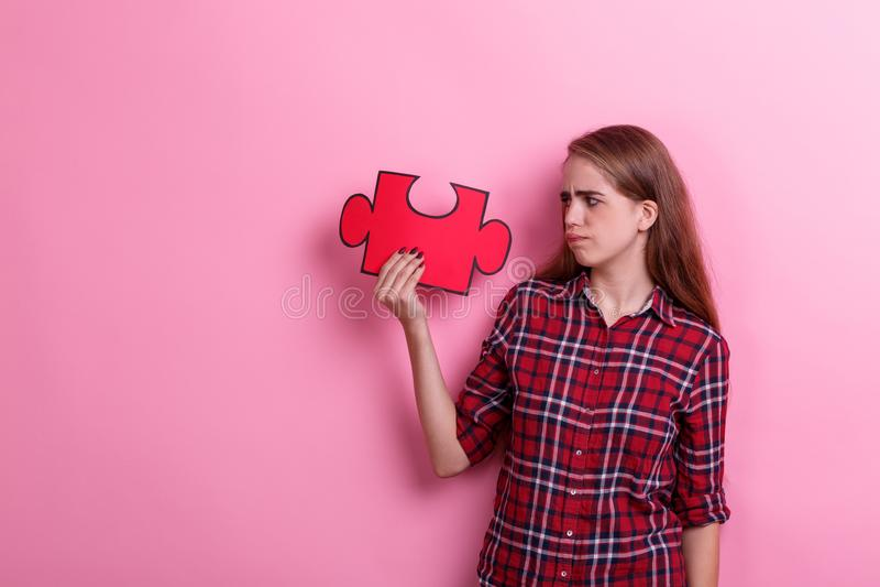 Het jonge ontevreden meisje, houdt een groot raadsel en bekijkt het Op een roze achtergrond royalty-vrije stock fotografie