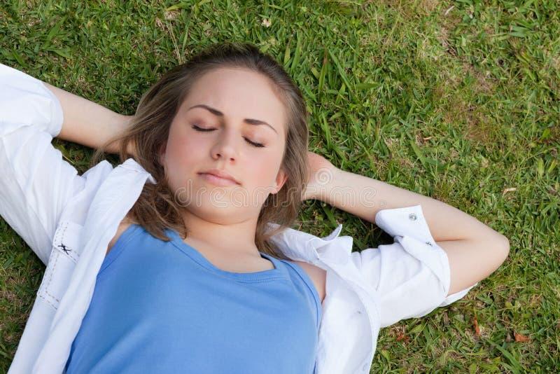 Het jonge ontspannen meisje sleeeping op het gras stock fotografie