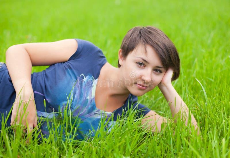 Het jonge ontspannen van de Vrouw op het groene gras stock fotografie