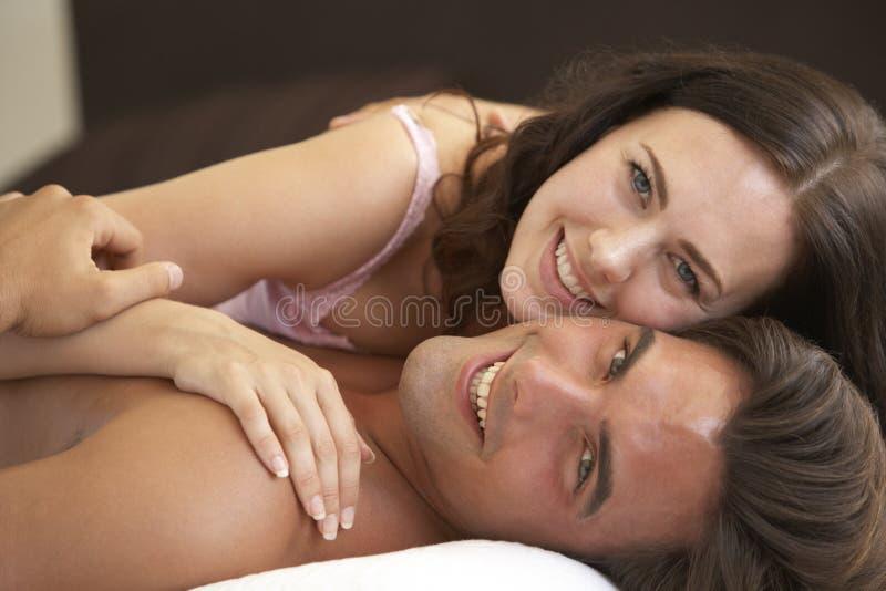 Het jonge Ontspannen van het Paar op Bed royalty-vrije stock afbeeldingen