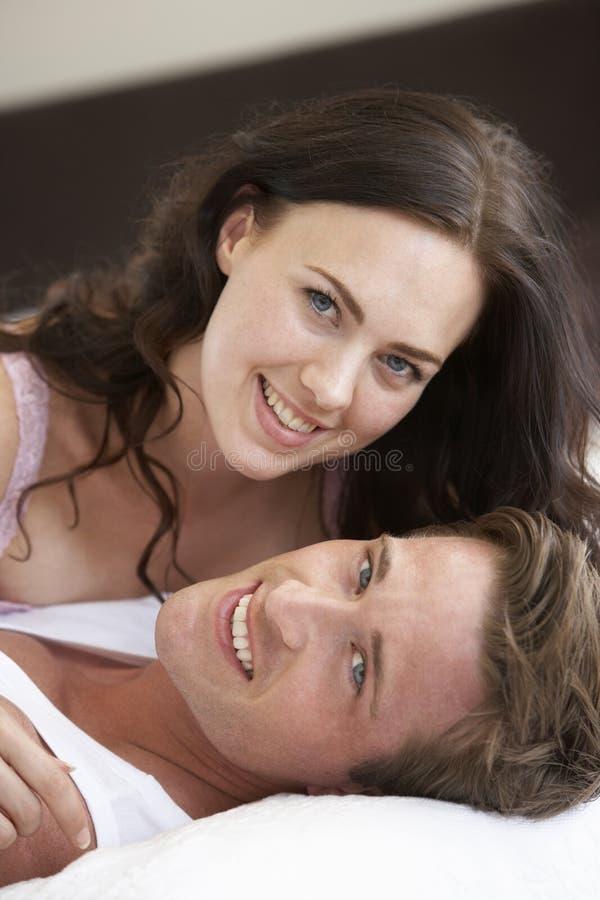 Het jonge Ontspannen van het Paar op Bed stock foto's