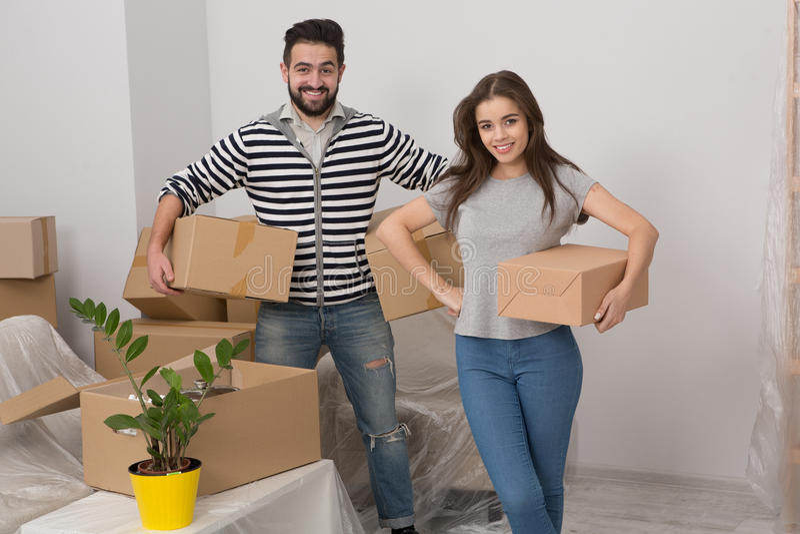 Het jonge paar beweegt zich in nieuw huis met partij van dozen stock foto's