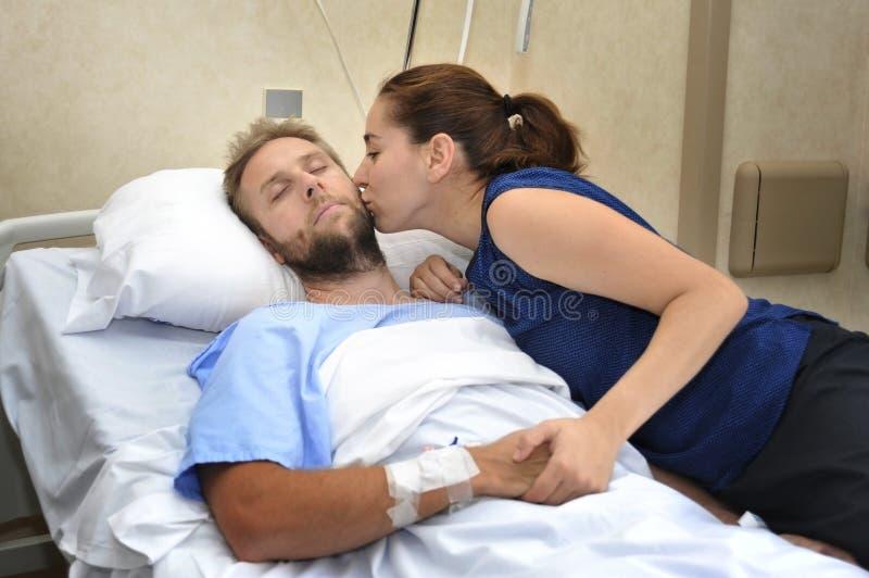 Het jonge paar bij de mens die van de het ziekenhuisruimte in bed liggen maakte zich vrouw ongerust die zijn hand het geven houde stock foto's