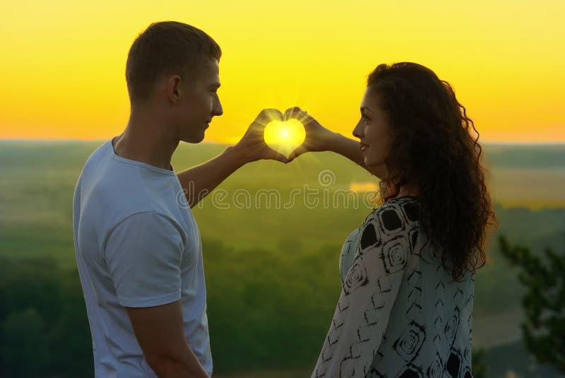 Het jonge paar bij zonsondergang maakt een hartvorm van handen, glanzen de stralen van zon door handen, mooi landschap en helder  royalty-vrije stock foto's