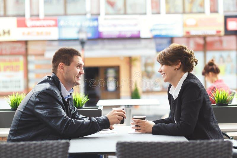 Het jonge paar brengt tijd in koffie door stock afbeeldingen