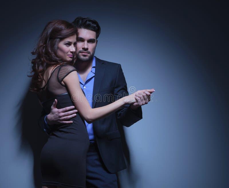 Het jonge paar in dans stelt stock foto's