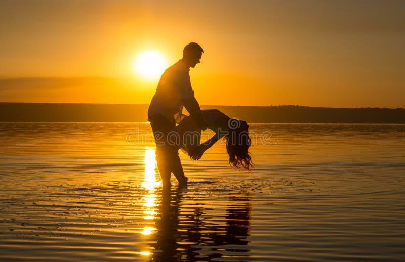Het jonge paar danst in het water op de zomerstrand Zonsondergang over het overzees Twee silhouetten tegen de zon Kalm en nog opp stock afbeeldingen