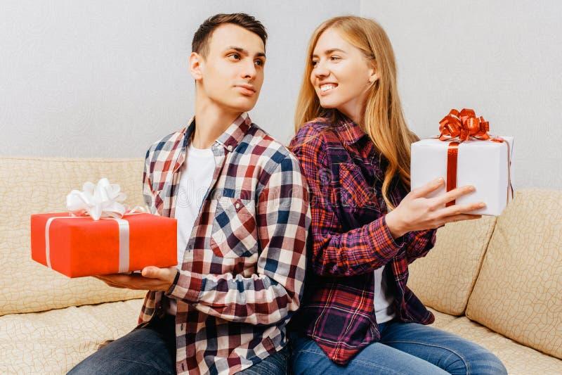 Het jonge paar, de man en de vrouw geven elkaar giften terwijl het zitten thuis op de laag, het concept van de valentijnskaartend stock fotografie