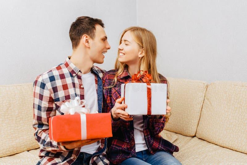 Het jonge paar, de man en de vrouw geven elkaar giften terwijl het zitten thuis op de laag, het concept van de valentijnskaartend royalty-vrije stock foto