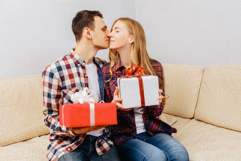Het jonge paar, de man en de vrouw geven elkaar giften terwijl het zitten thuis op de laag, het concept van de valentijnskaartend stock foto's