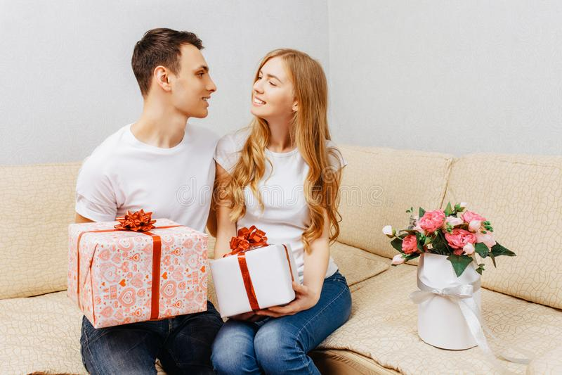 Het jonge paar, de man en de vrouw geven elkaar giften terwijl het zitten thuis op de laag, het concept van de valentijnskaartend stock afbeelding