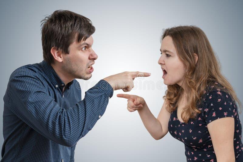 Het jonge paar debatteert en beschuldigt elkaar stock foto's