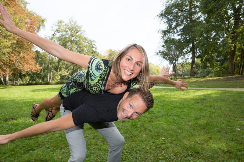 het jonge paar die en heeft pret bij het meisje van het stadspark met blondehaar berijdt op rug van knappe kerel lachen royalty-vrije stock foto's