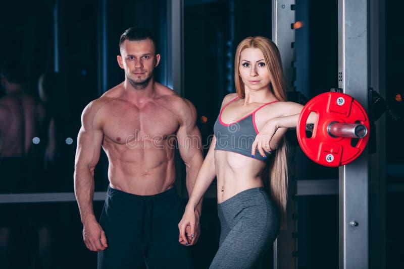 Het jonge paar die in gymnastiek met de gewichtenmens uitoefenen schijnt de persoonlijke trainer te zijn royalty-vrije stock afbeeldingen