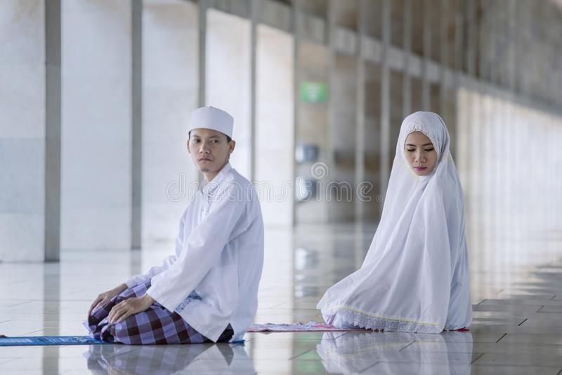 Het jonge paar doen bidt in de moskee stock afbeeldingen