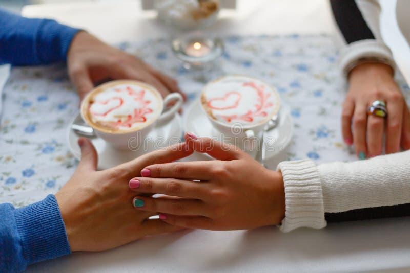 Het jonge paar drinkt koffie in liefde clasping handen over de lijst in koffie, close-up Romantische achtergrond, twee koppen van royalty-vrije stock afbeeldingen