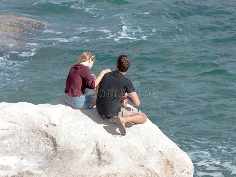 Het jonge paar, een kerel en een meisje, zitten op een rots, op de kusten van de Middellandse Zee, en kijken uit aan overzees in  royalty-vrije stock foto
