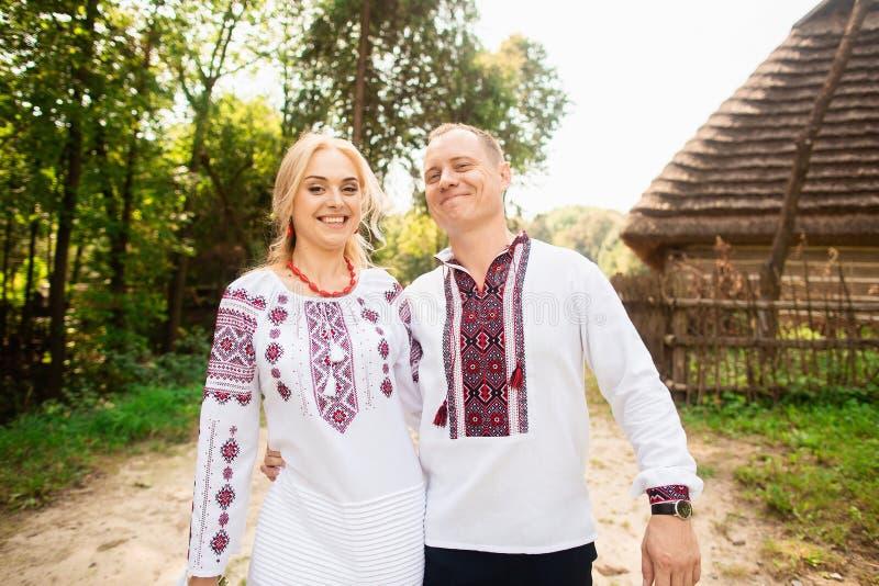 Het jonge paar in een traditionele Oekraïense kleding, heeft pret het besteden tijd in het Park stock fotografie