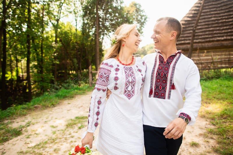 Het jonge paar in een traditionele Oekraïense kleding, heeft pret het besteden tijd in het Park royalty-vrije stock afbeelding