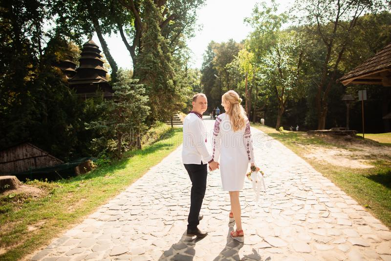 Het jonge paar in een traditionele Oekraïense kleding, heeft pret het besteden tijd in het Park Achter mening royalty-vrije stock foto's