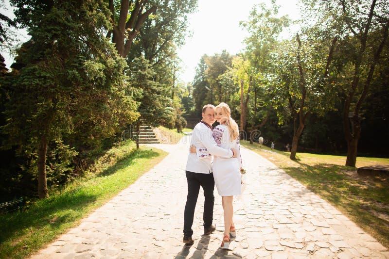 Het jonge paar in een traditionele Oekraïense kleding, heeft pret het besteden tijd in het Park Achter mening royalty-vrije stock afbeeldingen