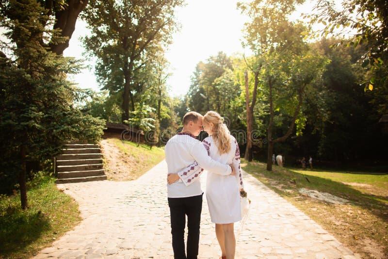 Het jonge paar in een traditionele Oekraïense kleding, heeft pret het besteden tijd in het Park Achter mening royalty-vrije stock afbeelding