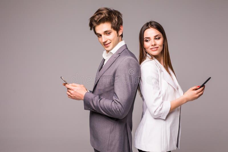 Het jonge paar gebruikt slimme telefoons en glimlacht terwijl status rijtjes op een grijze achtergrond bekijk camera royalty-vrije stock foto's