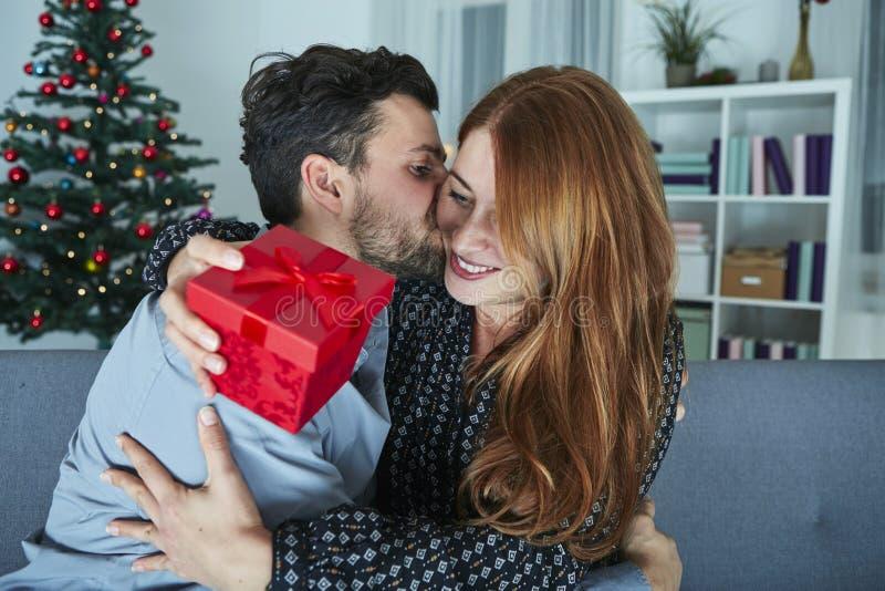 Het jonge paar is gelukkig met gift voor Kerstmis stock afbeeldingen