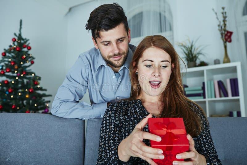 Het jonge paar is gelukkig met gift voor Kerstmis stock foto