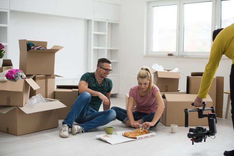 Het jonge paar heeft een pizzamiddagpauze op de vloer stock afbeelding