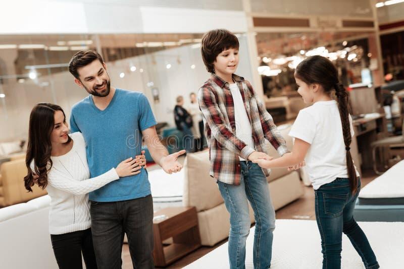 Het jonge paar kijkt als kinderen springt op matras in meubilairopslag Gelukkige familie die matrassen in opslag kiezen stock afbeelding