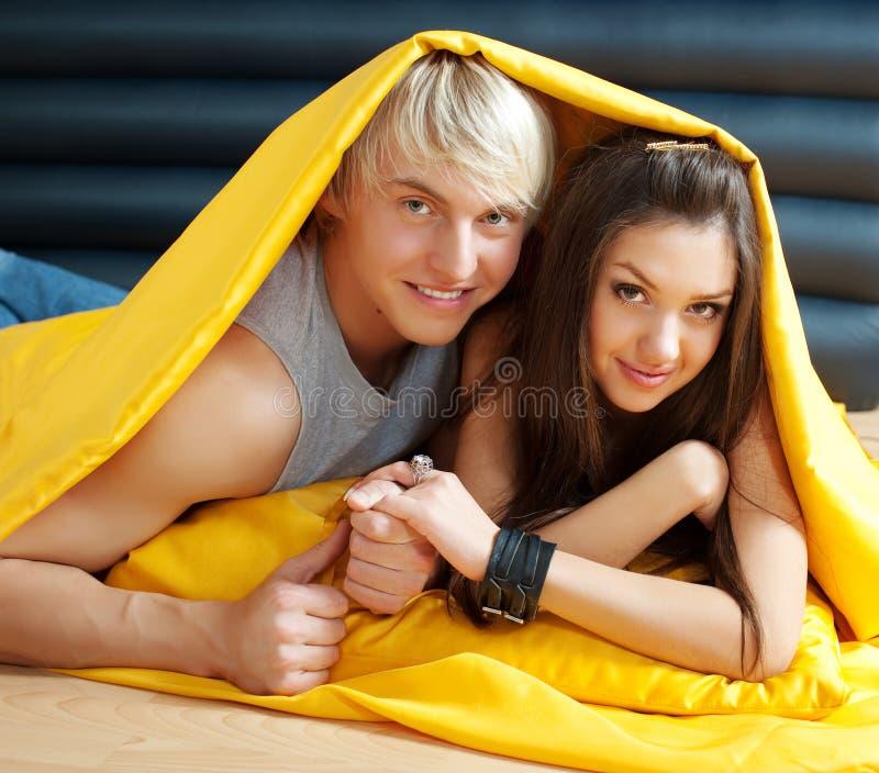 Het jonge paar kussen in bed stock afbeelding