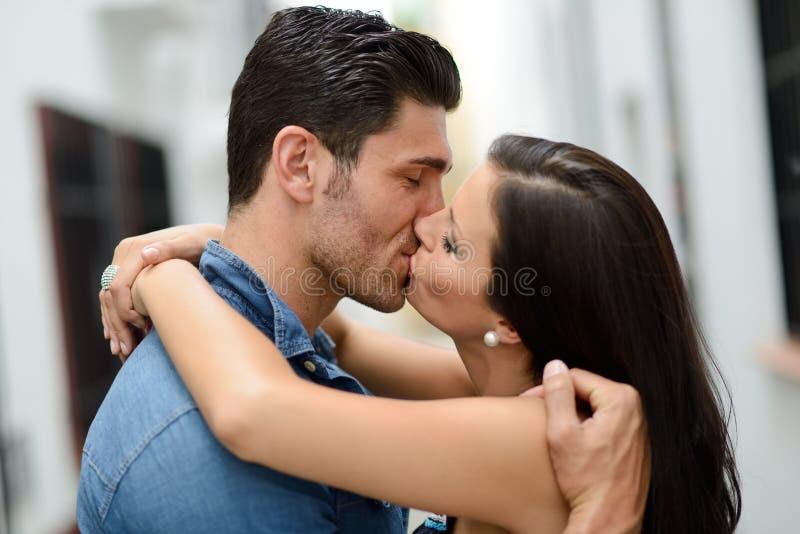 Het jonge paar kussen in de straat stock afbeelding