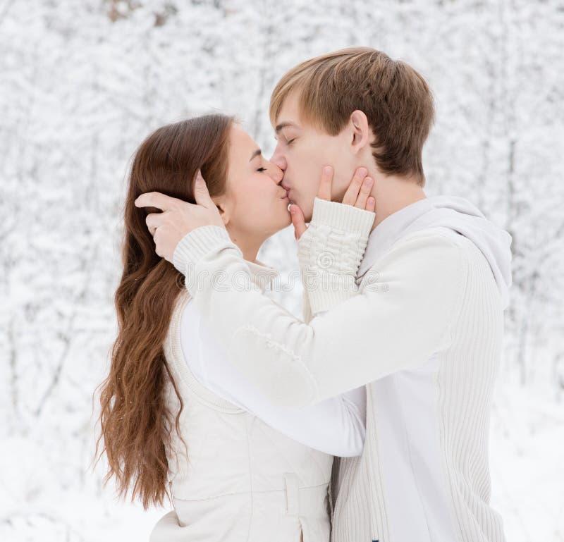Het jonge paar kussen in de winterbos stock afbeelding