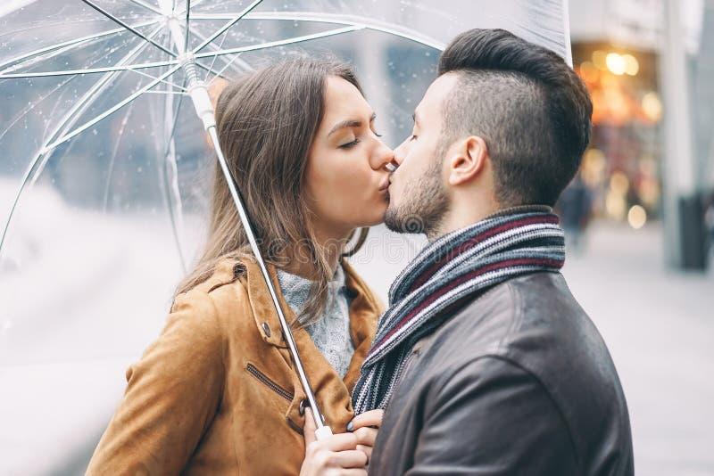 Het jonge paar kussen onder paraplu in regenachtige dag in het stadscentrum - Romantische minnaar die een teder ogenblik hebben o royalty-vrije stock afbeelding