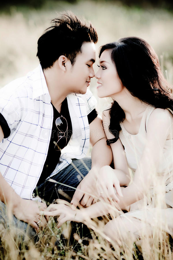Het jonge paar kussen op de zomergebied stock fotografie