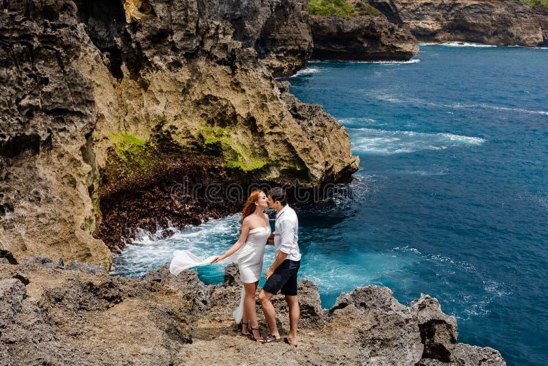 Het jonge paar kussen op een klip door het overzees stock fotografie
