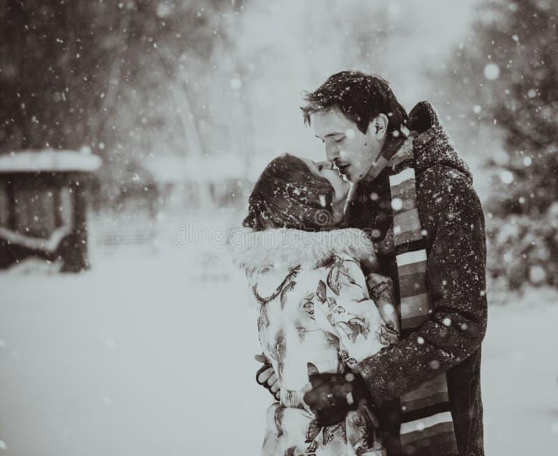 Het jonge paar kussen op sneeuw Rebecca 36 stock afbeeldingen