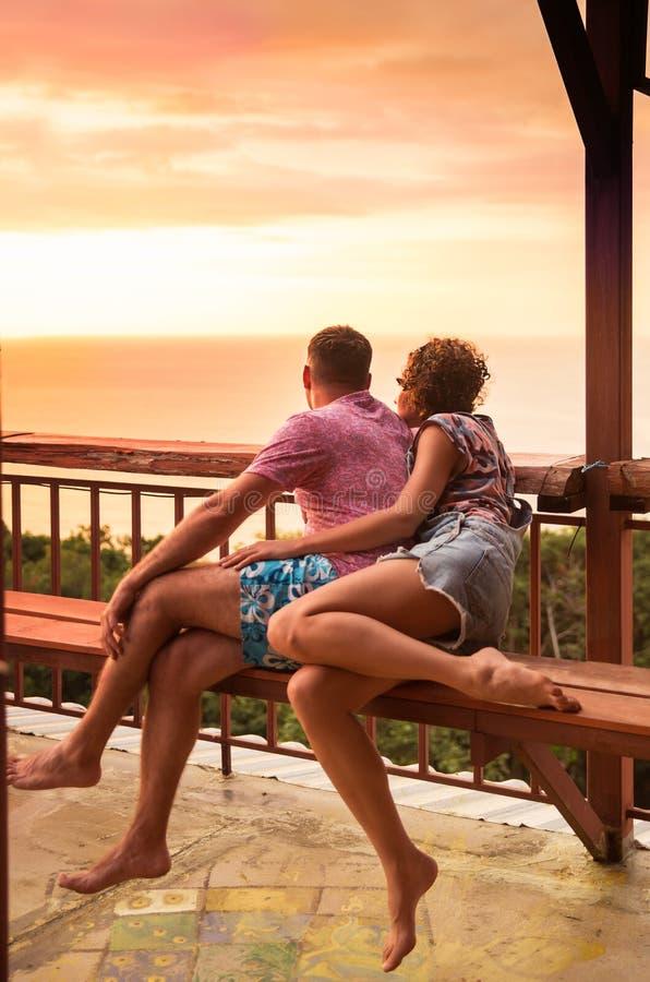 Het jonge paar let op tropische exotische zonsondergang stock foto's
