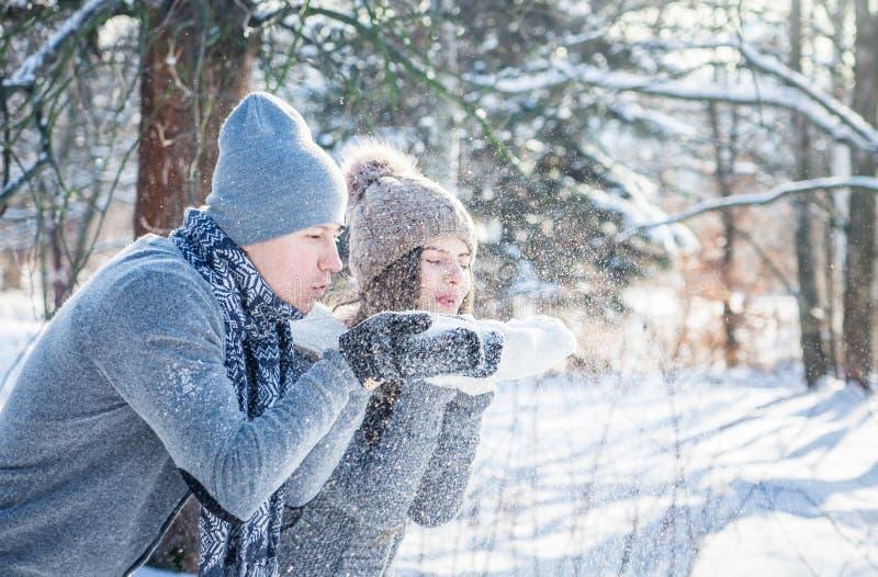 Het jonge paar in liefde blaast sneeuw royalty-vrije stock afbeeldingen