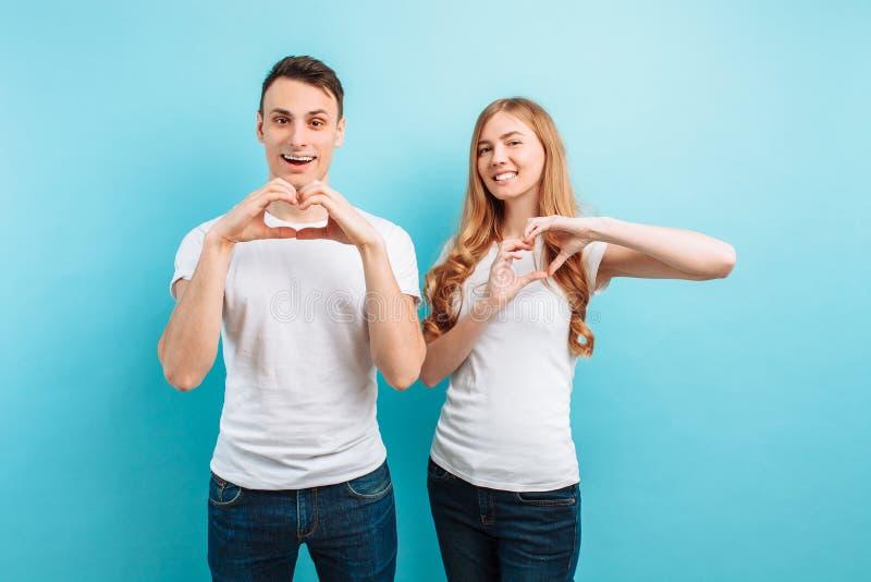 Het jonge paar in liefde, de man en de vrouw, tonen hart met handen, op blauwe achtergrond stock afbeelding